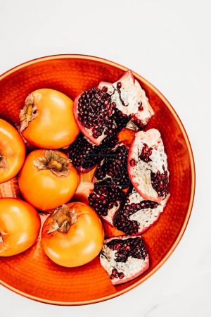 elevated view of persimmons and pomegranates on red plate isolated on white