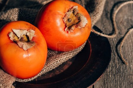two ripe persimmons on sackcloth on wooden table