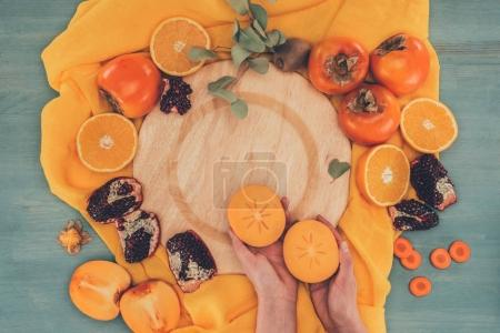 cropped image of woman holding two pieces of persimmon