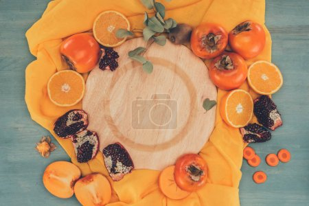 top view of wooden plate between persimmons with oranges and pomegranates