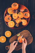 cropped image of woman cutting persimmon on wooden board