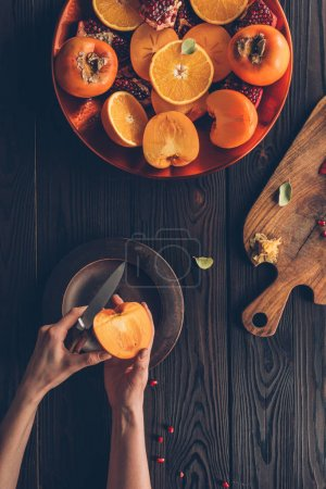 cropped image of woman cutting persimmon