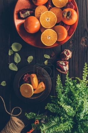 Photo for Top view of persimmons with cut oranges and pomegranates on plates on wooden table - Royalty Free Image