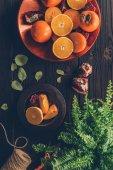 """Постер, картина, фотообои """"вид сверху хурма с резки апельсины, гранаты на пластины на деревянный стол"""""""
