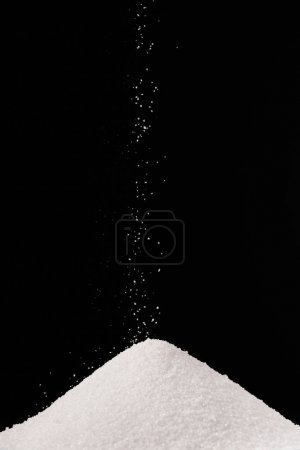 white sugar falling on pile isolated on black
