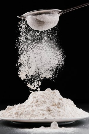 flour falling from sieve on pile isolated on black
