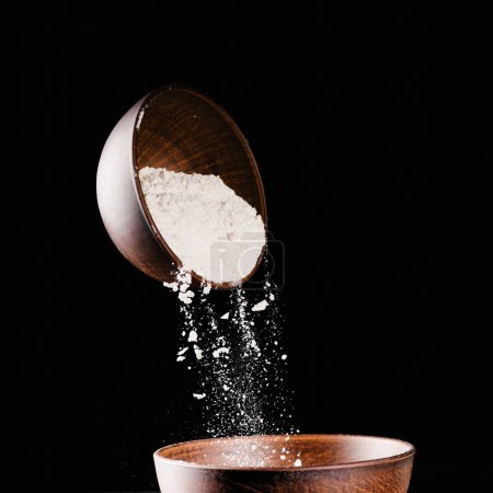 bowl with falling flour into another bowl isolated on black