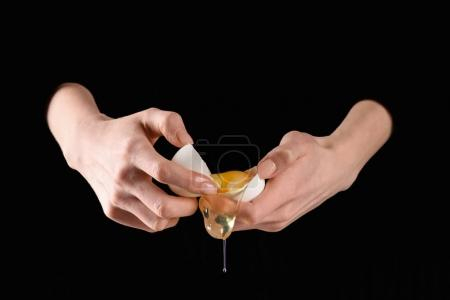 cropped image of woman holding broken chicken egg isolated on black