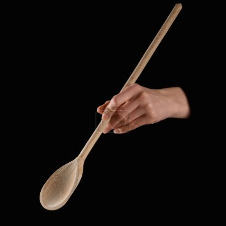 Photo for Cropped image of woman holding wooden spatula isolated on black - Royalty Free Image