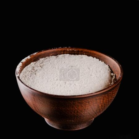 brown bowl with flour for dough isolated on black