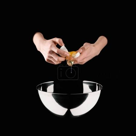 cropped image of woman holding broken chicken egg above bowl isolated on black