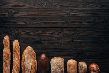 top view of arranged loafs of bread on wooden surface