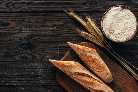 top view of arranged pieces of french baguette on cutting board, wheat and flour in bowl on wooden surface
