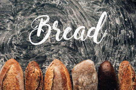 top view of arranged loafs of bread on dark tabletop with flour and bread lettering