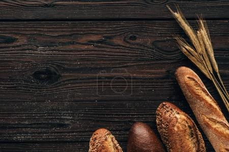 Photo for Top view of arranged loafs of bread and wheat on wooden surface - Royalty Free Image