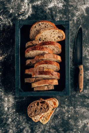 Photo for Top view of arranged pieces of bread in wooden box and knife on dark tabletop with flour - Royalty Free Image
