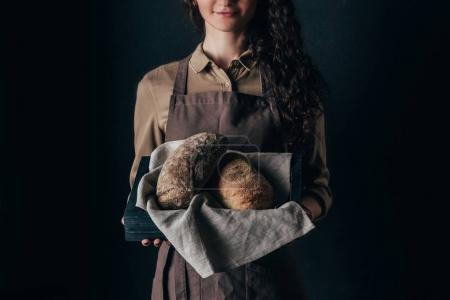 Photo for Cropped shot of woman holding wooden box with loafs of bread in hands isolated on black - Royalty Free Image