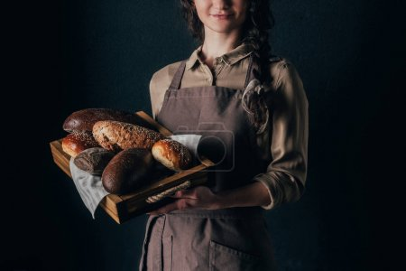 cropped shot of woman holding wooden box with loafs of bread isolated on black