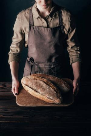 partial view of woman holding loafs of bread on wooden cutting board isolated on black