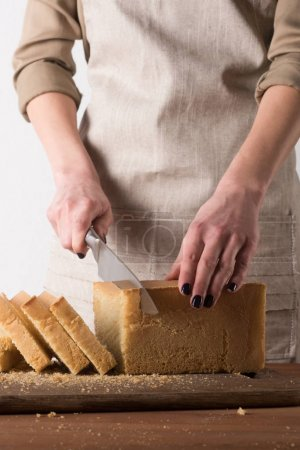 partial view of woman cutting bread into pieces on wooden cutting board