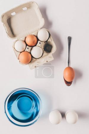 top view of glass with blue paint and chicken eggs on egg tray, easter concept