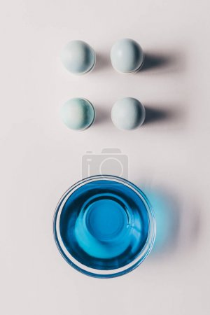 top view of four easter eggs on stands and glass of paint on white surface