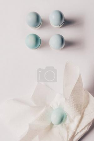 top view of chicken eggs on stands and on napkin after painting, easter concept