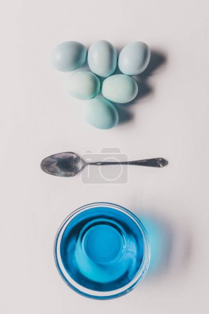 top view of glass with blue paint, spoon and chicken eggs on white surface, easter concept