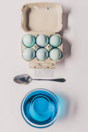top view of glass with blue paint, spoon and chicken eggs in tray, easter concept