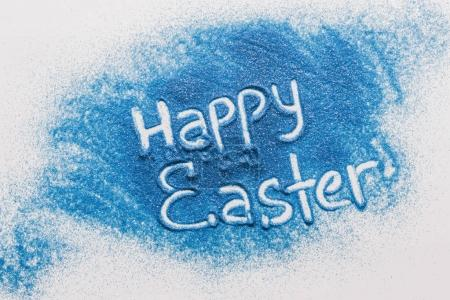 top view of happy easter sign made of blue sand on white surface