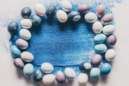 top view of painted easter eggs and blue sand on white surface