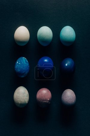 collection of nine colored painted easter eggs on dark surface