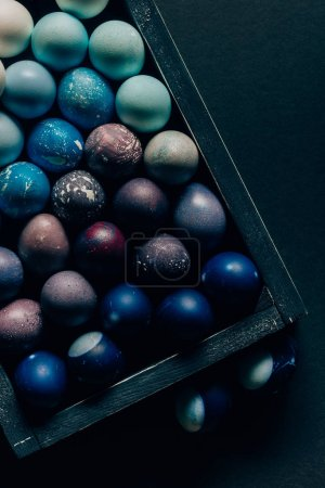 top view of colored painted easter eggs in wooden box on dark table