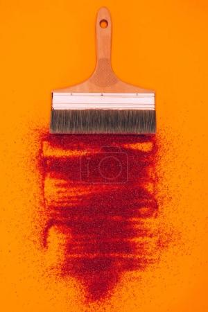 top view of red sand for decoration and brush isolated on orange