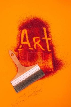top view of art sign made of red sand and brush isolated on orange