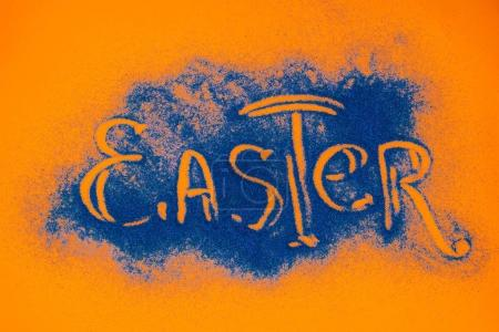 top view of easter sign made of blue sand on orange surface
