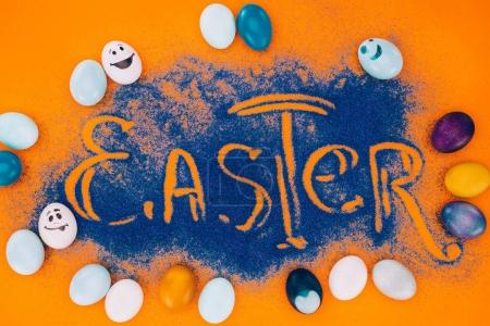 top view of easter sign made of blue sand with painted eggs on orange