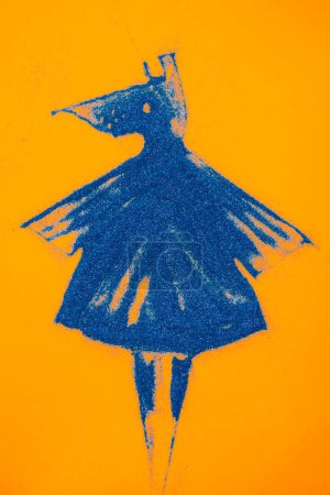 top view of blue easter chicken made of sand isolated on orange