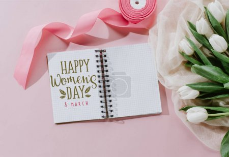 Photo for Top view of HAPPY MOTHERS DAY greeting in notepad, pink ribbon and white tulips on pink - Royalty Free Image