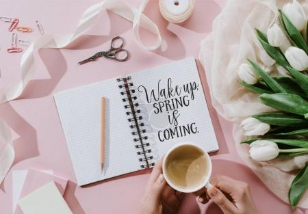 cropped view of woman holding coffee cup on pink surface with tulips and WAKE UP. SPRING IS COMING iscription in notepad
