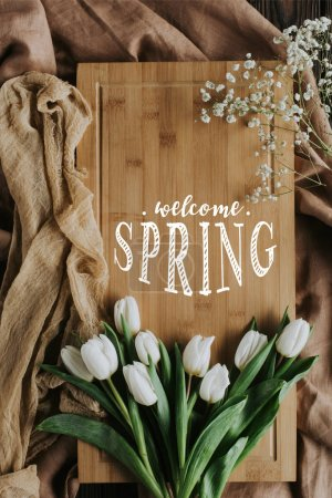 top view of white tulips and WELCOME SPRING lettering on wooden board and tablecloth