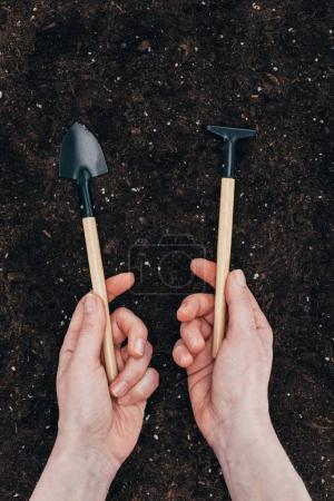 cropped shot of human hands holding small gardening tools above soil