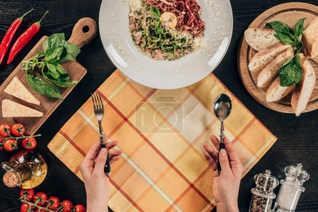 Photo for Cropped image of woman holding fork and spoon near plate with pasta - Royalty Free Image