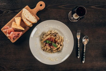 top view of pasta with meat and glass of red wine on table