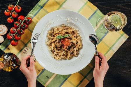 cropped image of woman holding fork and spoon and going to eat pasta