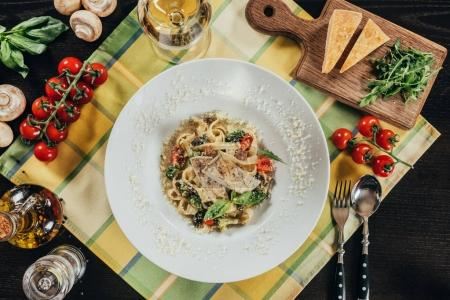 top view of pasta with pike perch fillet and grilled vegetables on plate