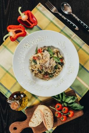 top view of pasta with pike perch fillet and grilled vegetables on table
