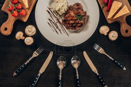 Photo for Top view of beef steak on plate and utensil on table - Royalty Free Image