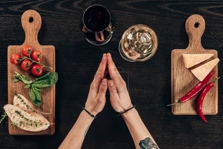 cropped image of woman sitting at table with wine and parmesan cheese