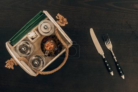 Photo for Top view of wooden box with olive oil and pepper grinder on wooden table - Royalty Free Image
